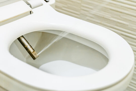 Domestic toilet seat with water jet spray close up. Bathroom technologies and invetions. Higiene and personal cleanliness.