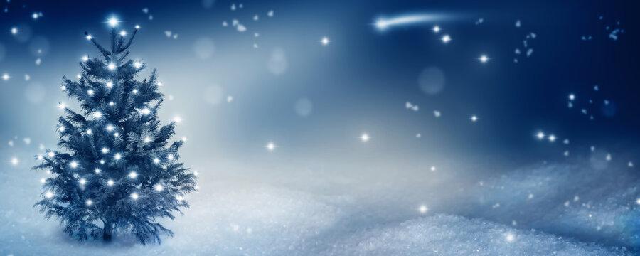idyllische weihnachtsnacht mit leuchtendem Christbaum im schnee
