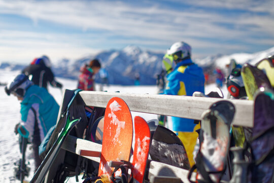 View of a wooden rack for skis, full of skis and snowboards, on the top of a high mountain with the beautiful landscape of dolomiti mountains and people skiing, alpe tognola, san martino di castrozza
