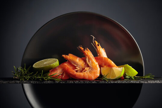 Boiled shrimps with rosemary and lime on a black background.