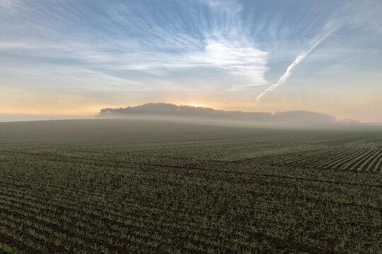Nebliger Sonnenaufgang über einem Feld in Bayern