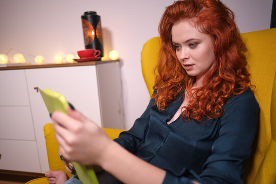 Woman  using a tablet on line at home sitting on a yellow in the living room at home . Covid isolation