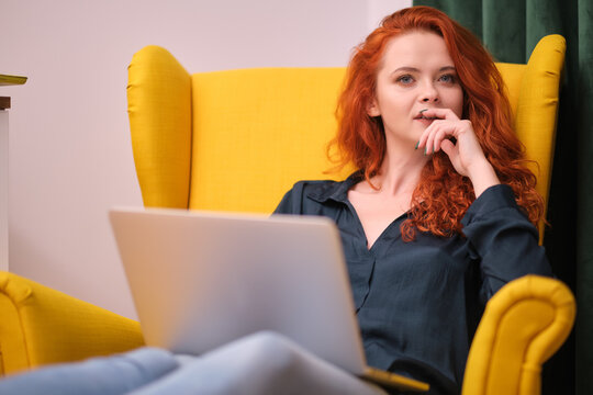Redhead young woman using laptop at home. covid isolation. home office