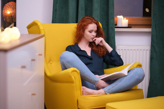 Relaxed happy woman reading a book sitting on a couch at home