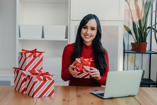 Portrait of a smiling young woman looking at camera holding Christmas gift at home