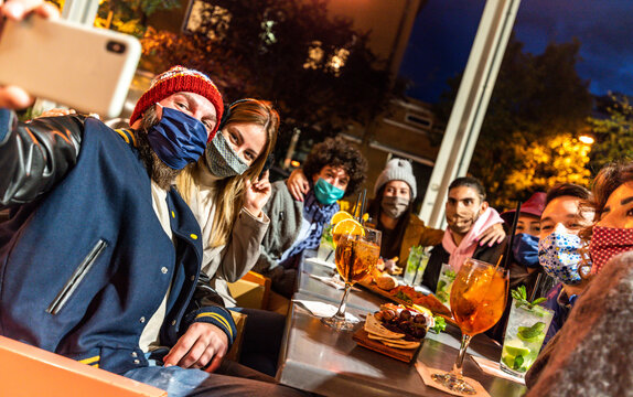 Group of happy friends taking a selfie at cocktail bar - Young people covered by face masks having fun at restaurant - New normal lifestyle concept.