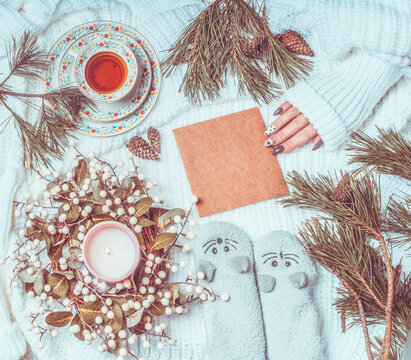 Winter and  Christmas lifestyle flat lay. Women hand holding craft paper greeting card lies on white knitted blanket with fir branches, candles , cup of tea and cozy warm socks . Top view