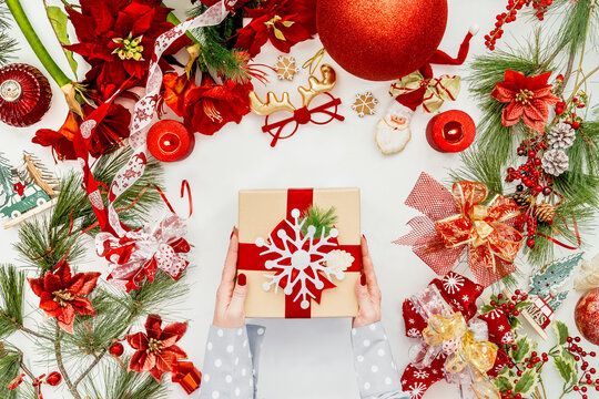 Women hand holding Christmas gift box on white desk with various  Christmas decoration . Top view