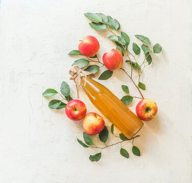 Composing with homemade apple juice in glass bottle with apples and green leaves on white background. Top view