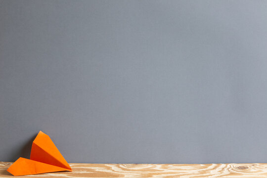 Orange paper plane on wooden table. Gray background copy space