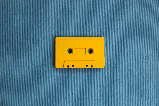 Yellow audio cassette tape on blue fabric background. top view, copy space