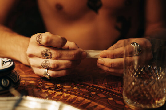 Close Up Of Man's Tattoed Hands Rolling A Joint