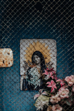 Holy icon and flowers behind rusty grate close up