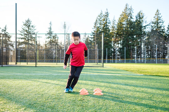 Asian Kid Exercise in an Outdoor Field Using Training Cones