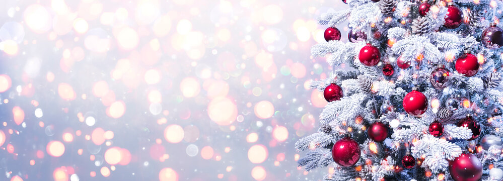Abstract Holiday Background - Snowy Christmas Tree With Red Baubles With Shiny Defocused Lights