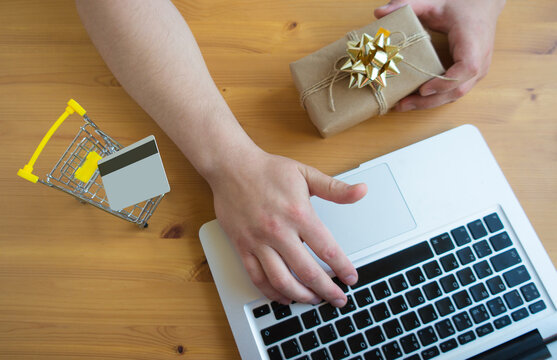 A man orders for gifts on the Internet on a laptop without leaving home with a credit card. Online shopping concept.