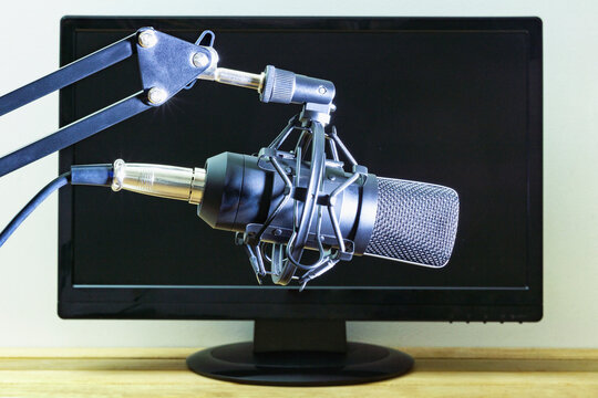 Studio microphone on the background of a computer monitor.