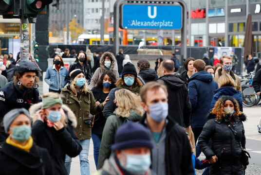 People wear protective face masks as they walk at Alexanderplatz shopping area amid the coronavirus disease (COVID-19) outbreak in Berlin