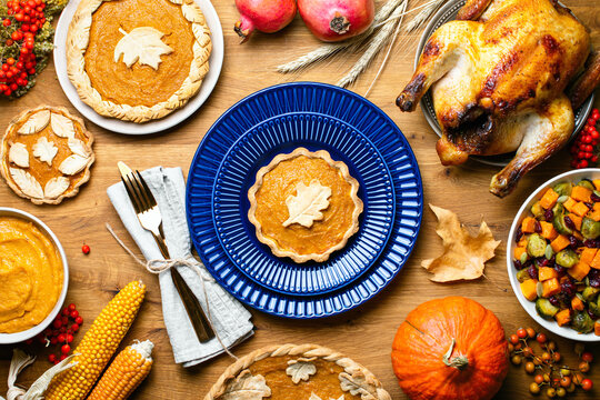 Pumpkin mini pie served on a dark blue plate, top down view of Thanksgiving table setting