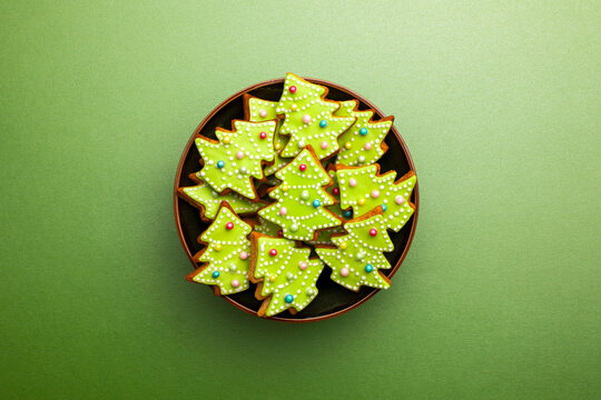Christmas tree-shaped gingerbread cookies in a bowl, top down view