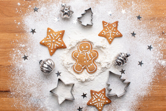 Traditional Christmas gingerbread cookies lying on a floured kitchen table