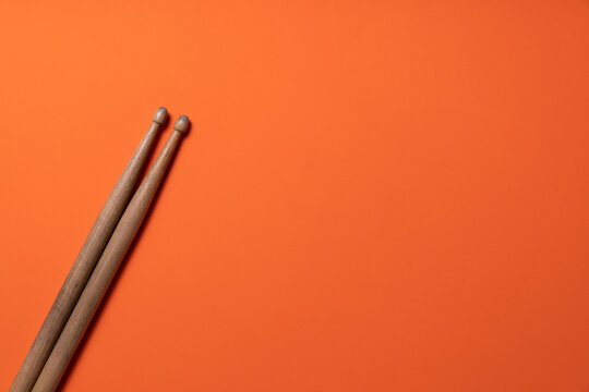 Drum stick on orange table background, top view, music concept