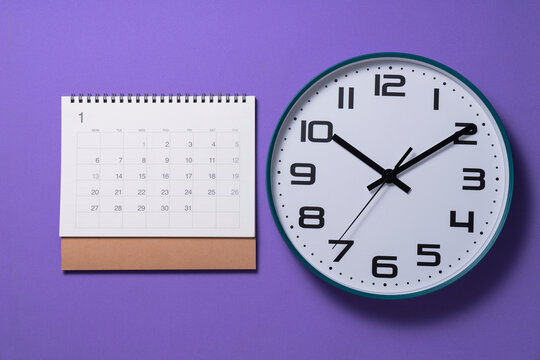 close up of calendar page and clock on the purple table background, planning for business meeting or travel planning concept