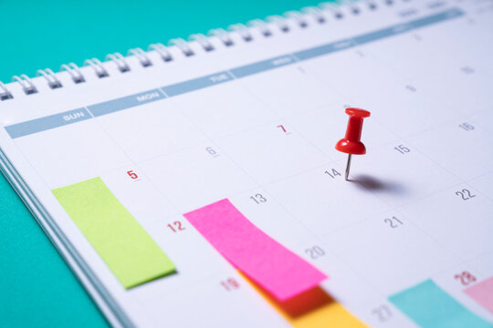 close up of pin on calendar page on the green table background, planning for business meeting or travel planning concept