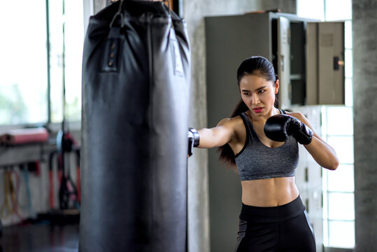 Attractive female boxer training boxing at gym