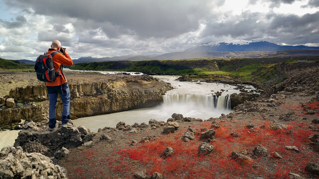 Landscape Photographer Capturing an Image of Thjofafoss Waterfall with Hekla Volcano on Top, Iceland