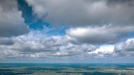 Fotobehang - Beautiful high altitude clouds flying over summer forest landscape. Aerial drone hyperlapse, 4K UHD.