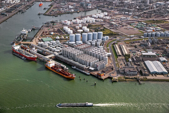 Aerial view of an oil tanker moored at an oil storage silo terminal port.