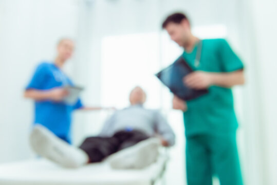 Defocused Image Of Healthcare Workers And Patient At Hospital