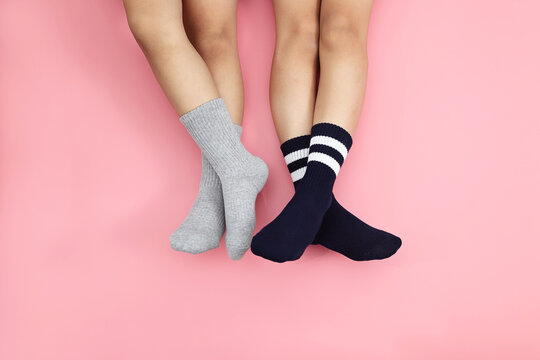 Low Section Of Children Wearing Socks While Resting Over Colored Background