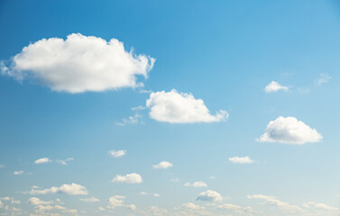 Wall Mural - Blue sky background with white fluffy clouds in the fresh sunny day.