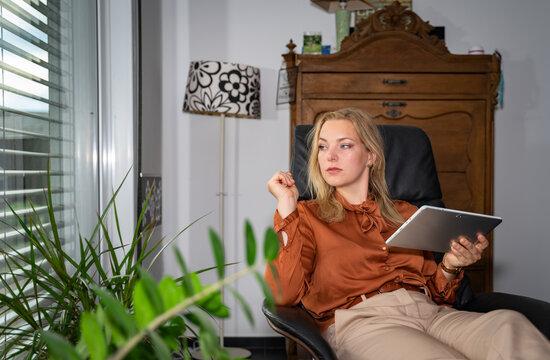 Attraktive Frau surft zuhause mit einem Tablet-PC  im Internet, Symbolfoto.