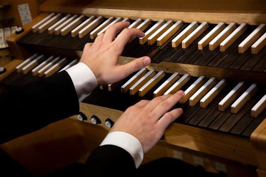 Close up view of a organist hands playing a pipe organ