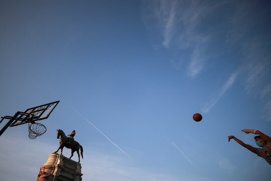A person plays basketball on a hoop set up at the base of the monument to Confederate General Robert E. Lee, in Richmond, Virginia