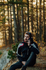 Fototapeta A young man uses a military compass for orientation in nature, talking on the phone, surrounded by fog.