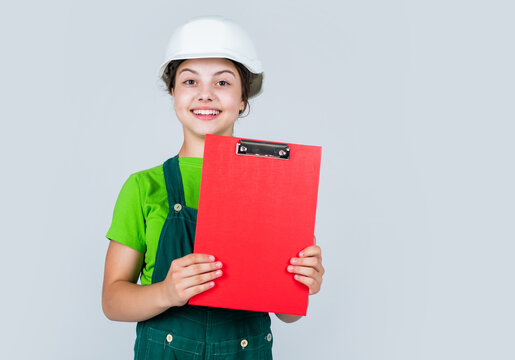 kid wear helmet on construction site. teen girl builder with building document. child on repairing work. concept of renovation in workshop. busy professional carpenter. Builder engineer architect