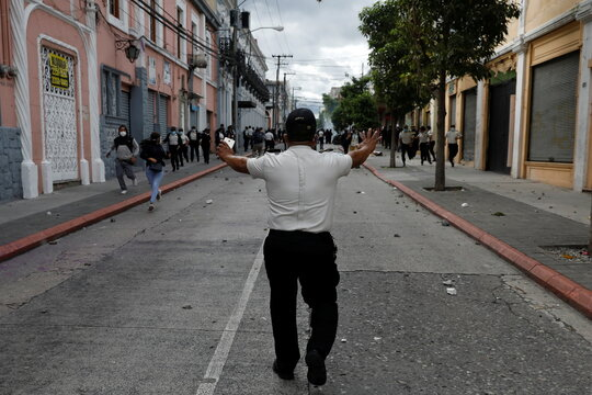 A police officer shouts at demonstrators during a protest demanding the resignation of President Alejandro Giammattei, in Guatemala City