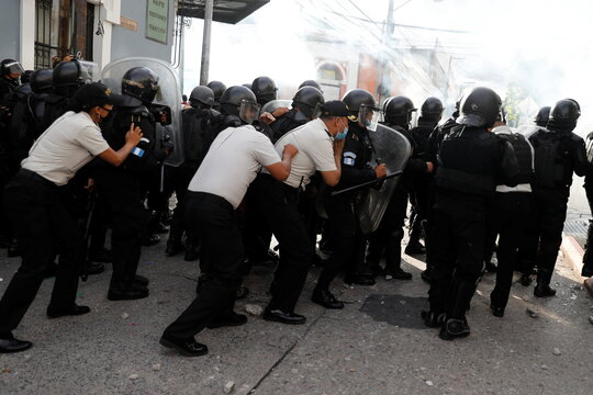 Police officers take cover behind riot police during a protest demanding the resignation of President Alejandro Giammattei, in Guatemala City