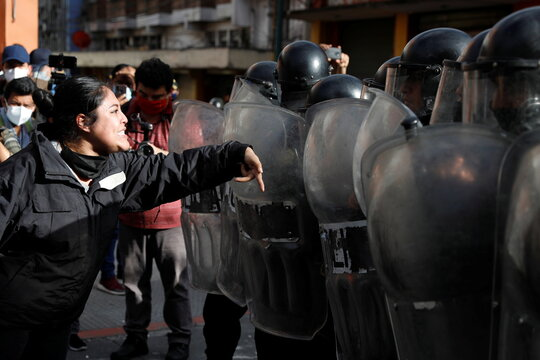 A demonstrator shouts at riot police during a protest demanding the resignation of President Alejandro Giammattei, in Guatemala City