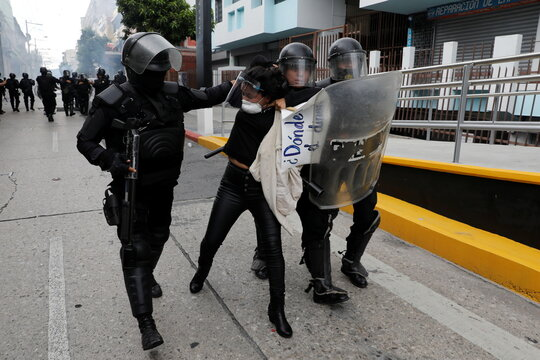 Riot police detain a demonstrator taking part in a protest demanding the resignation of President Alejandro Giammattei, in Guatemala City