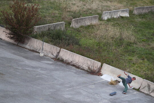 A skateboarder falls down while attempting to land a trick along a vacant parking lot in the Riverfront neighborhood in Wilmington