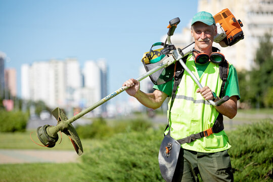 Municipal gardener landscaper senior man worker with gas grass trimmer equipment on sunlight city background