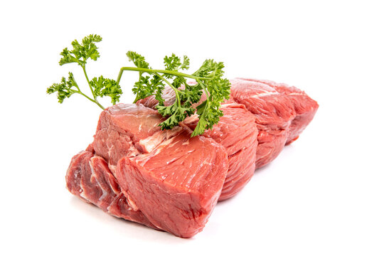 A cut of beef sirloin tip roast with parsley garnish isolated on white