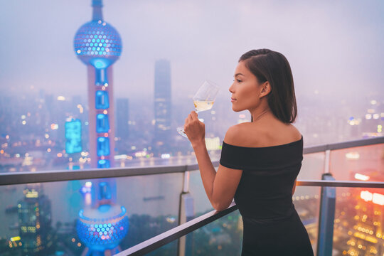 Luxury Shanghai lifestyle Asian woman drinking white wine in on China Travel. Elegant model in black dress at terrace view of the city, high end living.