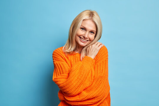 Beautiful smiling blonde woman embraces herself looks with tender satisfied expression tilts head wears warm knitted sweater isolated over blue background. Charming aged female model feels comfort