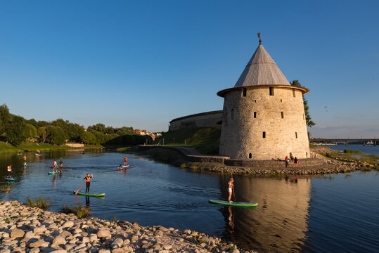 Pskov, Russia: august 21, 2020:  SUP surfers on Pskova river. Towers and wall of Pskov Kremlin at background.